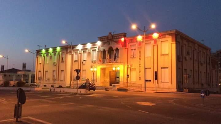 """Barcellona PG. Palazzo Longano illuminato col Tricolore. Materia: """"Torneremo presto ad abbracciarci!"""""""